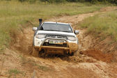 White Toyota Triton DHD crossing mud obstacle — Foto Stock