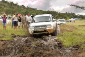 White Toyota Triton DHD crossing mud obstacle — Stock Photo