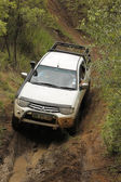 White Toyota Triton DHD crossing mud obstacle — Stockfoto