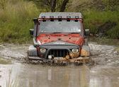 Turuncu jeep rubicon crossing çamurlu su birikintisi ezmek — Stok fotoğraf