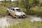 White Toyota Raider Hilux 3.0L crossing muddy pond — Stock Photo