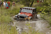 Crush oranje jeep rubicon oversteken modderige vijver — Stockfoto