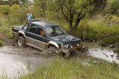 Viridian Green Mitsubishi Colt Rodeo Twin Cab crossing muddy pon — Stok fotoğraf