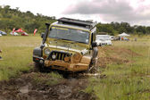 Gecko Pearl Green Jeep Wrangler Rubicon crossing mud obstacle — Stock Photo