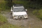 White Mazda BT-50 4x4 3L crossing muddy pond — Stockfoto