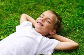 Smiling little boy lying in a field — Stock Photo