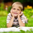 Beauty smiling child boy reading book outdoor on green grass fie — Stock Photo