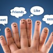 Foto Stock: Happy group of finger smileys with social chat sign and speech b