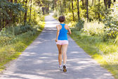 Sporty young woman runner running on the road in forest — Stock Photo