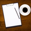 Clipboard with blank page and cup of coffee — Stock Photo #7730387