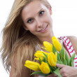Blonde woman with flowers yellow spring tulips — Stock Photo