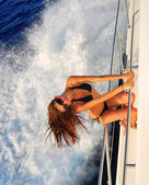 Slim sexy brunette woman in sunglasses sailboat yacht — Stock Photo