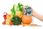 Diabetes concept glucose meter in hand fruits, vegetables — Stock Photo