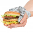 Burger cheeseburger in hands with measure tape — Stock Photo