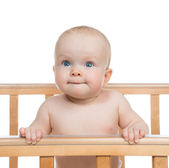 Infant child baby boy in wooden bed looking up — Stock fotografie