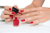Woman hands doing manicure red nails — Stock Photo