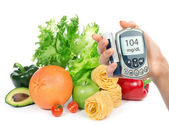 Glucose level blood test meter in hand and healthy organic food  — Stock Photo