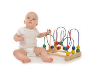 Child baby toddler sitting and playing wooden educational toy — Stock Photo