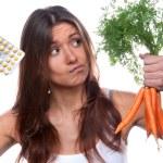 Woman choose between organic fresh carrots medical tablet pills — Stock Photo