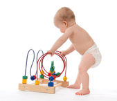 Child baby toddler standing and playing wooden educational toy  — Stock Photo