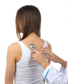 Doctor nurse auscultating young patient woman by stethoscope — Stock Photo