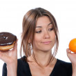 Woman comparing unhealthy donut and orange fruit — Stock Photo #47316081