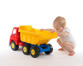 Infant child baby boy toddler big toy car truck red yellow  — Stock fotografie