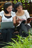 Girls Sharing laptop and magazine — Stock Photo