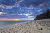 Sunset on the sandy beach of a tropical island — Stock Photo