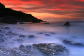 Colorful sunset in a quiet ocean cove — Stok fotoğraf