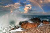 Rainbow over stormy sea — Stock Photo