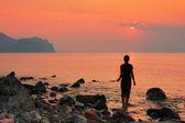 The girl on the beach watching the sea sunrise — Stock Photo