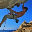 Rock climber on a safety rope on blue sky background — Stock Photo #38236945