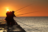Fishermen on sunrise on the pier — Stock Photo