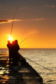 Silhouette of fishermen at sunrise — Stock Photo