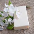 Bar of soap with white flowers on sacking cloth — Stockfoto