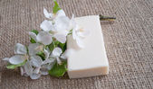 Bar of soap with white flowers on sacking cloth — Stock Photo