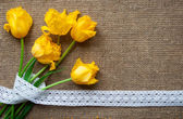 Postcard with yellow flowers and handmade tape on sacking cloth — Stock Photo