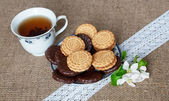 Cookies on a plate with cup of tea with flowers on sacking cloth — Stock Photo