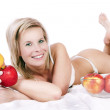 Cheerful girl in bed surrounded by apples. — Stock Photo #26167995