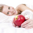 Cheerful girl in lingerie on the bed, an apple in his hand. — Stock Photo