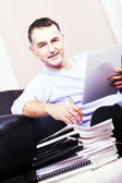 Young man, sitting on the couch next to, and work. — Stock Photo