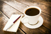 Cup of coffee and notebook next to it. — Stock Photo