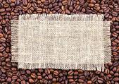 En påse med kaffebönor vävnad under. — Stockfoto