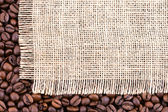 With roasted coffee beans on rustic fabric. — Stock Photo