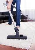Happy man is cleaning in the modern room with vacuum. — Stock Photo