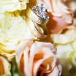 A pair of gold rings and bouquets. — Stock Photo