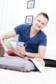 Un homme assis sur le tapis lire confortablement. — Photo