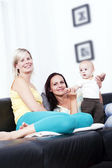Mother and girlfriend in the living room of identical baby. — Stock Photo