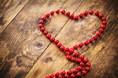Heart shape pearl necklace, a wooden background. — Stock Photo